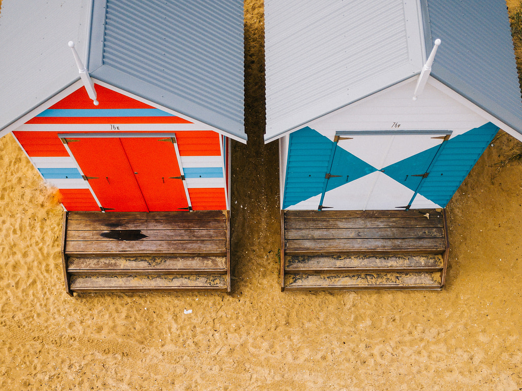aerial photo of two blue and red wooden sheds on sand