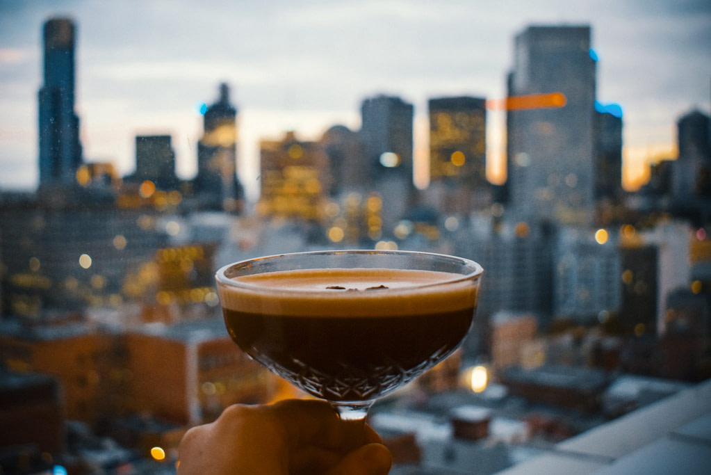 hand holding cocktail glass with city skyscrapers in background