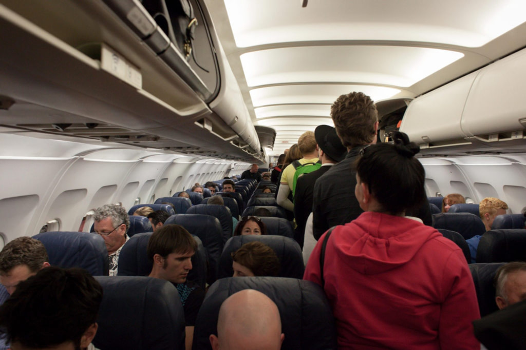 queue of people down aisle boarding aeroplane with many already seated