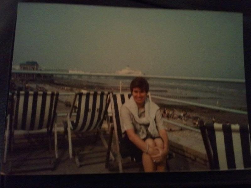 woman sitting on beach chair with brighton pier in background in 1980's