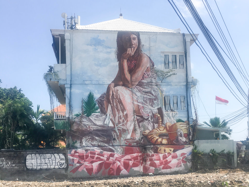 pained mural of girl sitting at beach on building wall