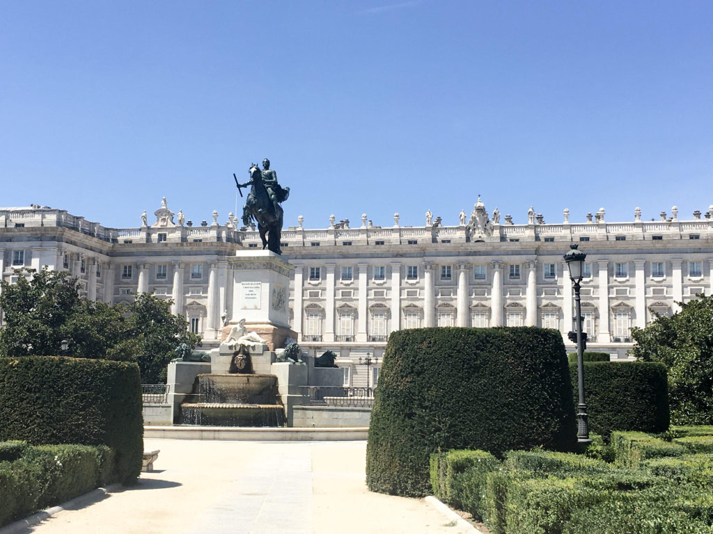 Royal Palace of Madrid with statue and garden