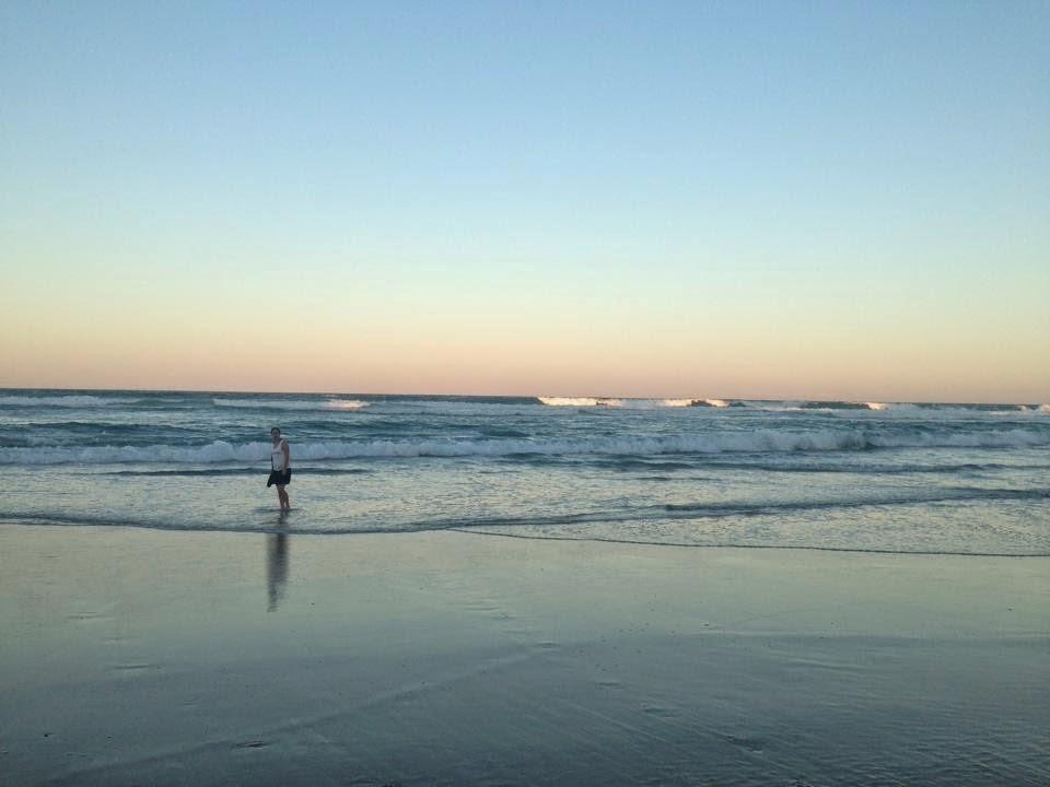young woman at sunset in shallow waves on gold coast beach