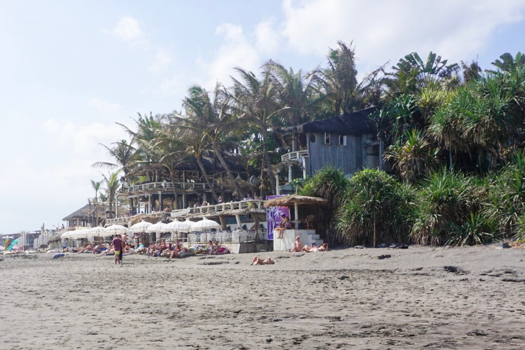 hut style beach bar surrounded by palm trees with white sun umbrellas out front