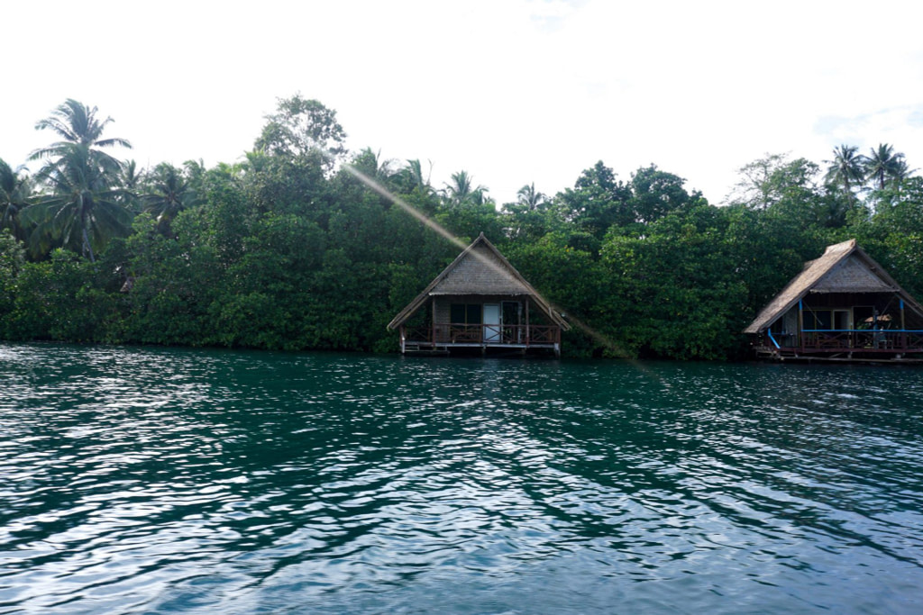 two simple bungalows at the edge of an island viewed over water from a boat