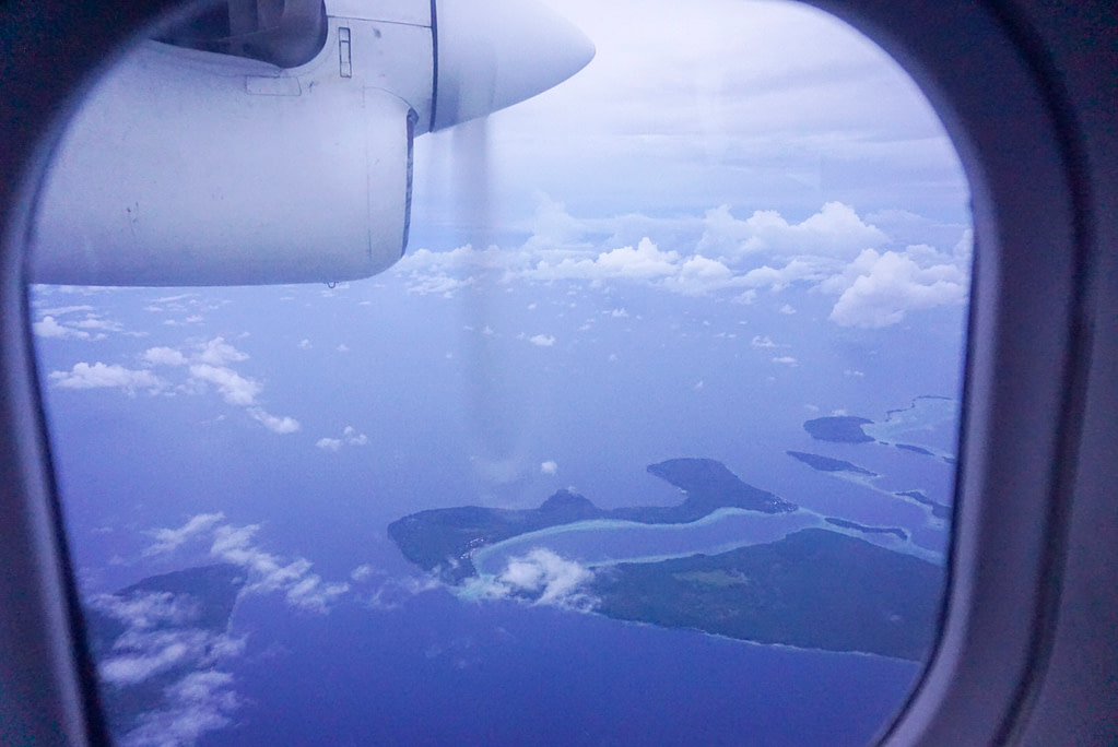 view of pacific islands and plane propeller out window in blue sky