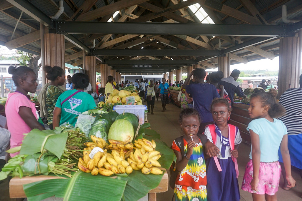 three young girls walking around fruit markets in pacific island town