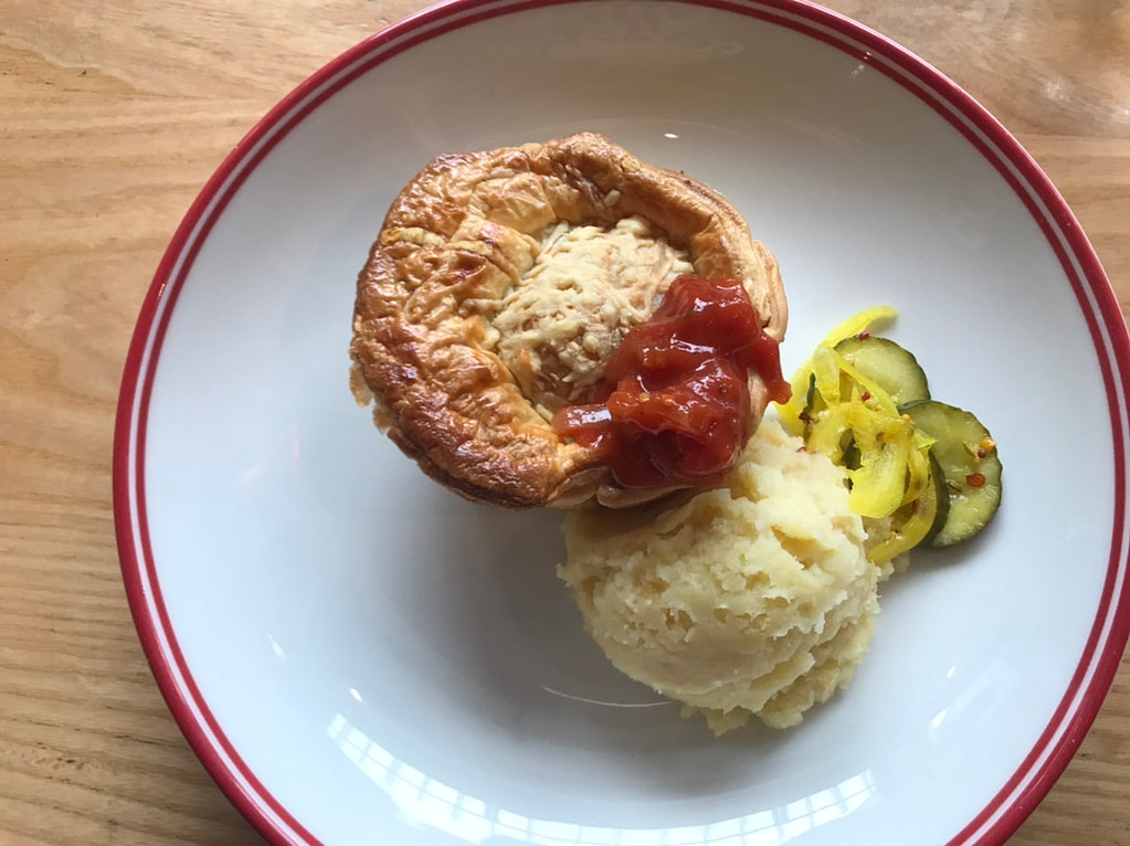 Creamy mushroom, truffle and parmesan pie with chutney, mashed potato and pickles on white dish with red rim at Pickle & Pie Wellington