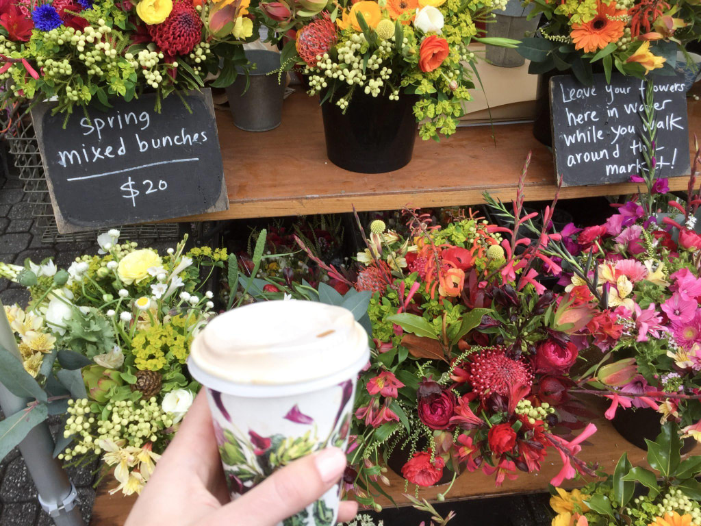 hand holding takeaway coffee cup in front of flowers sold at market