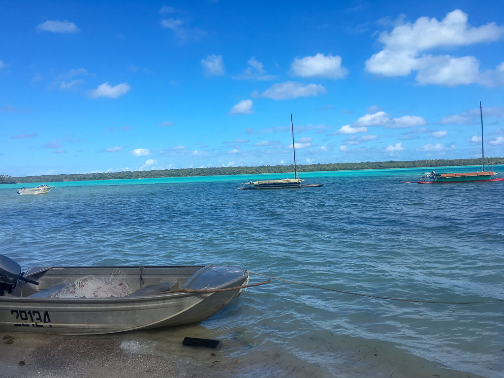 three handmade boats on blue water with a speed boat grounded on sand in foreground