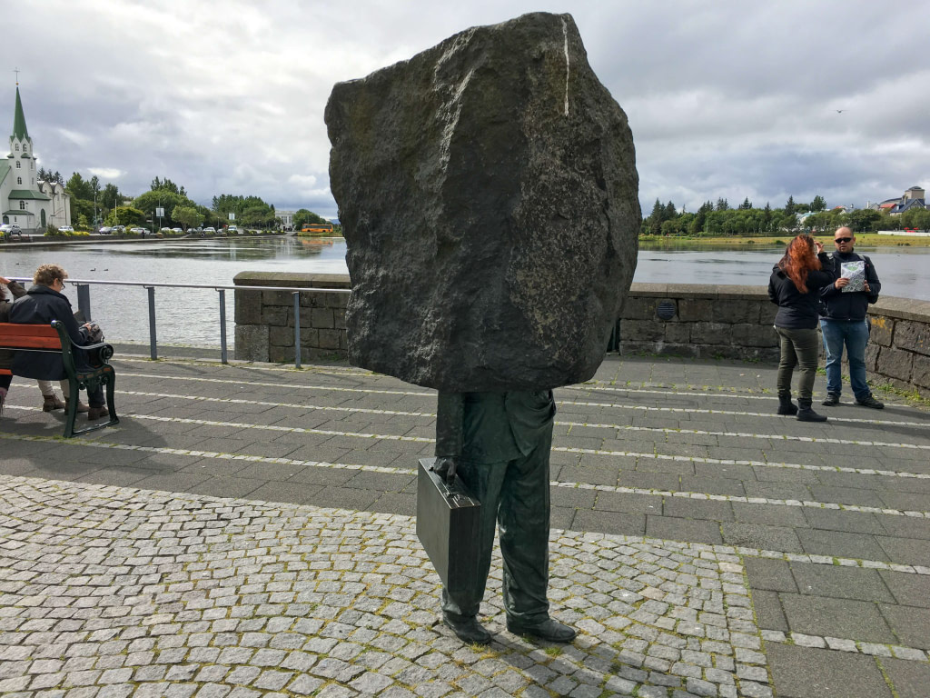 Statue of man holding briefcase with rock on his head on lake front in Reykjavik Iceland. Monument to the Unknown Bureaucrat.
