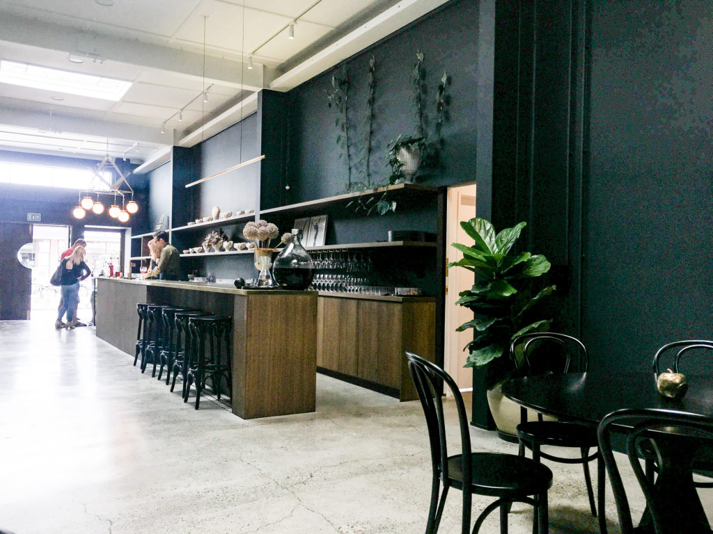 long bar in gin distillery with concrete floor, two greet plants, a table with four chairs, barstools and glasses