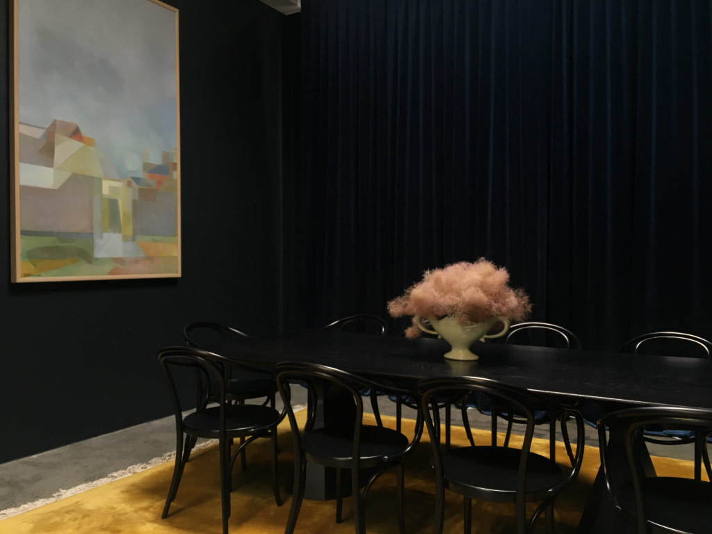 Dark room with long black table, 9 chairs, pink floral centerpiece, large artwork on wall and yellow carpet