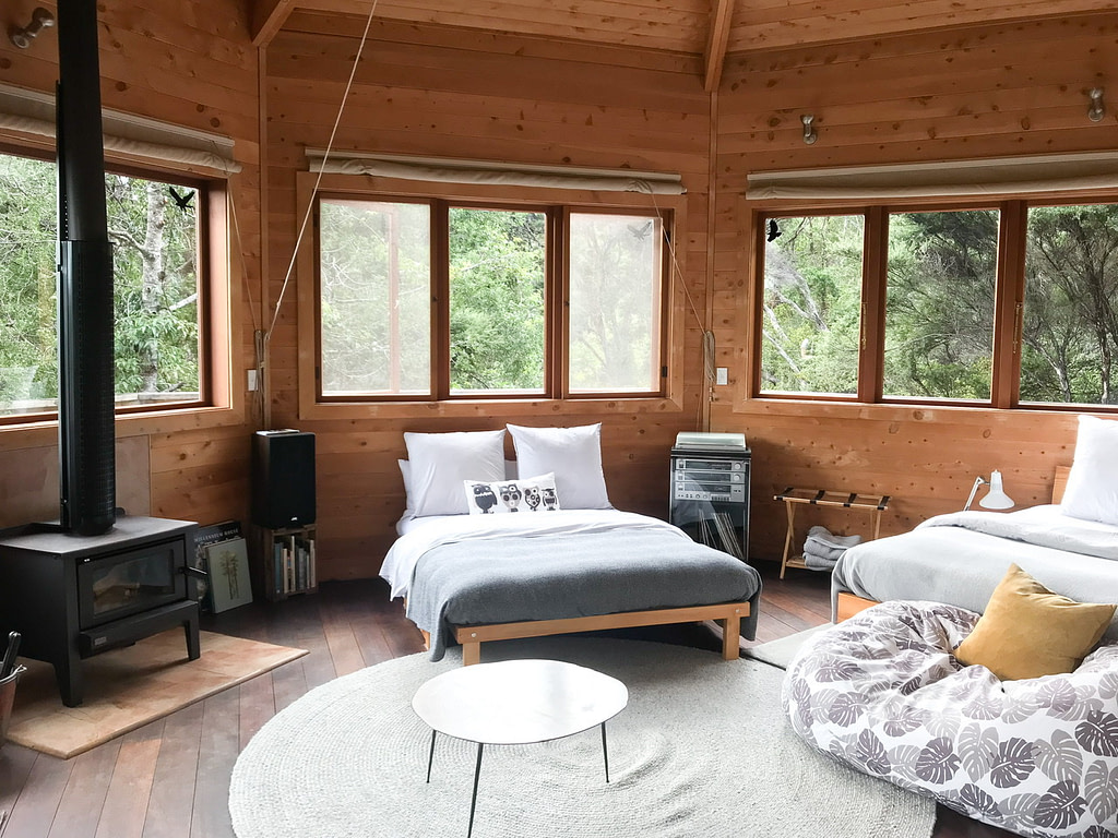 Interior of Away treehouse Waiheke Island accommodation with fire, two beds, bean bag and wooden paneled walls