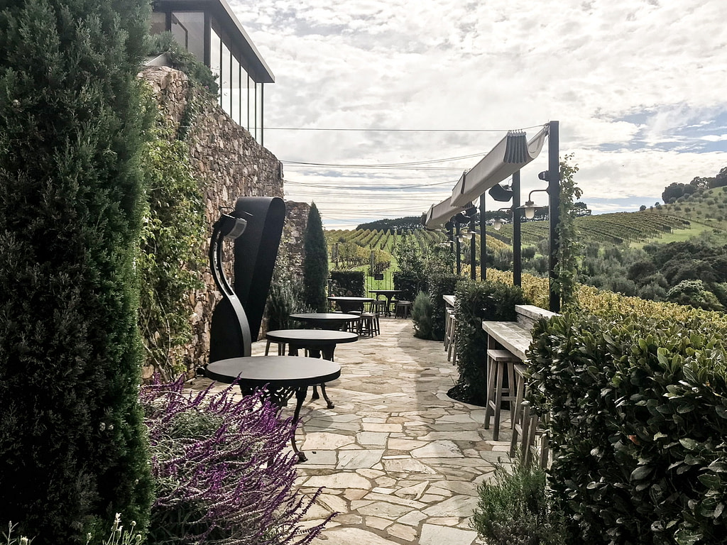 Exterior of Tantalus Estate Waiheke Island cellar door with tables, brickwork and wine vines in background