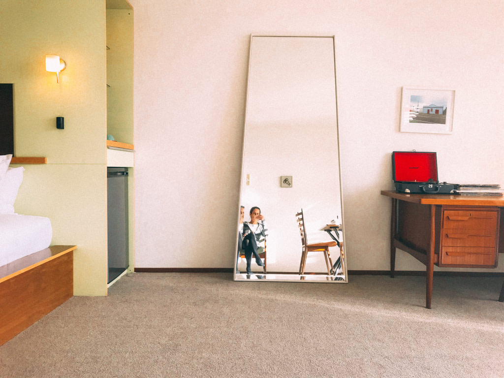 young woman reflected in mirror in suite at Ohtel botique hotel wellington