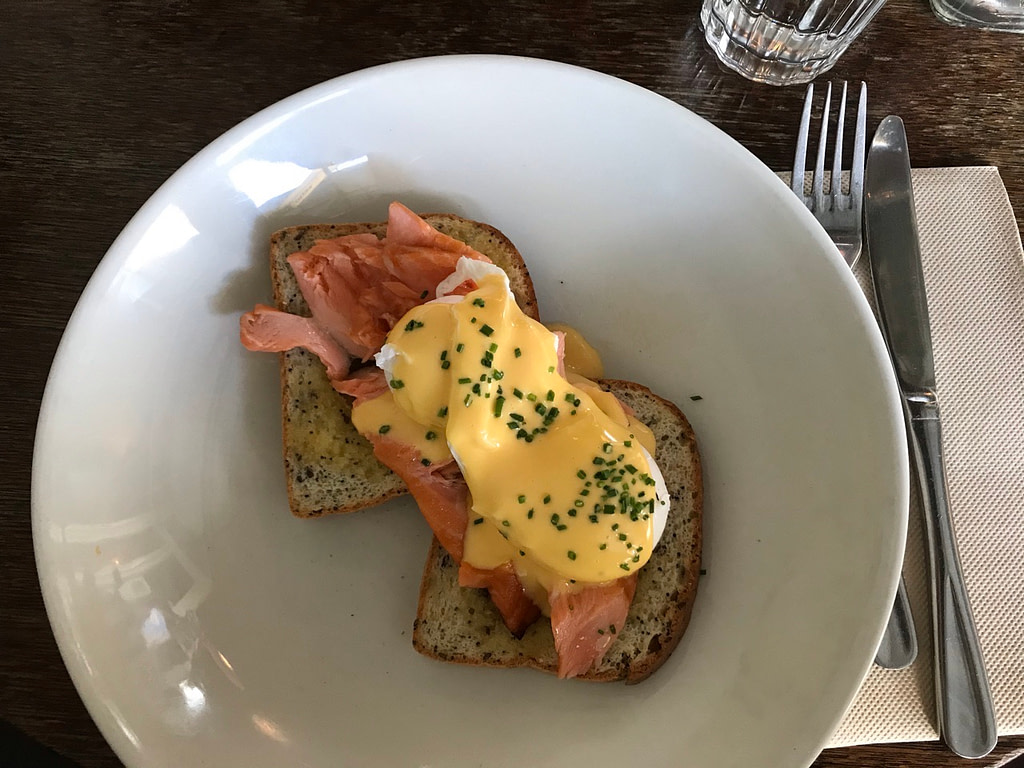 Eggs Montreal with house smoked salmon and hollandaise on two pieces of gluten free bread on white plate with knife and fork