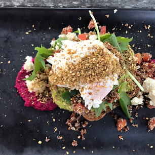 Smashed avocado on seeded sourdough with beetroot hummus, topped with a quinoa tomato salsa, feta, dukkah and a poached egg