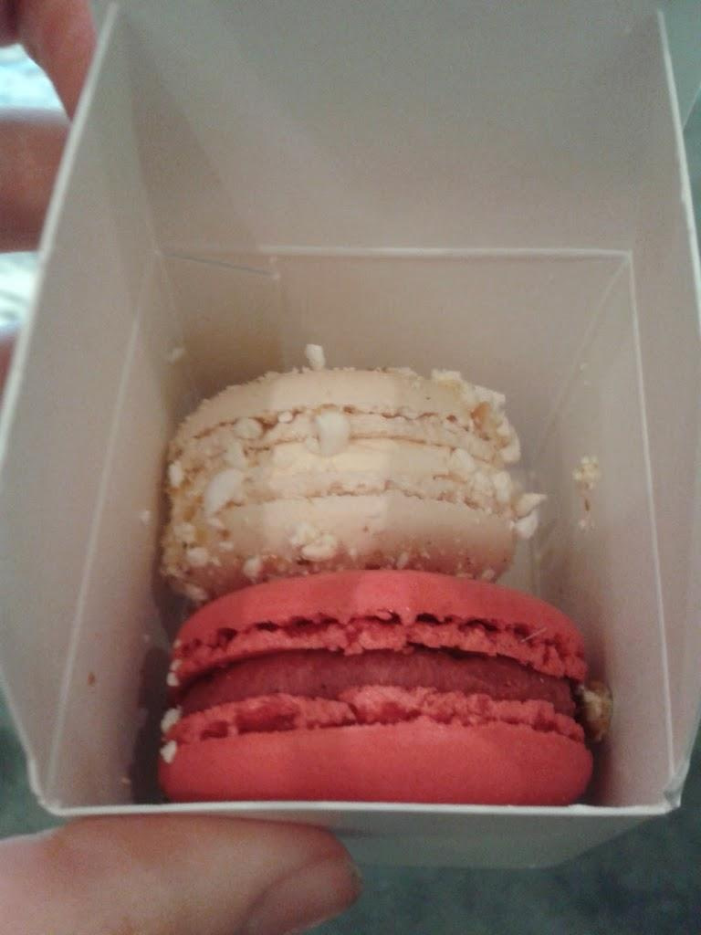 one pink and one white macaroon inside a small white box