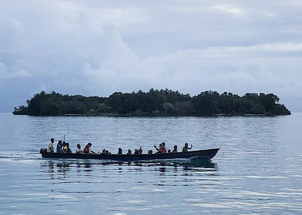 group of people in a small boat with two islands in background in the Solomon Islands