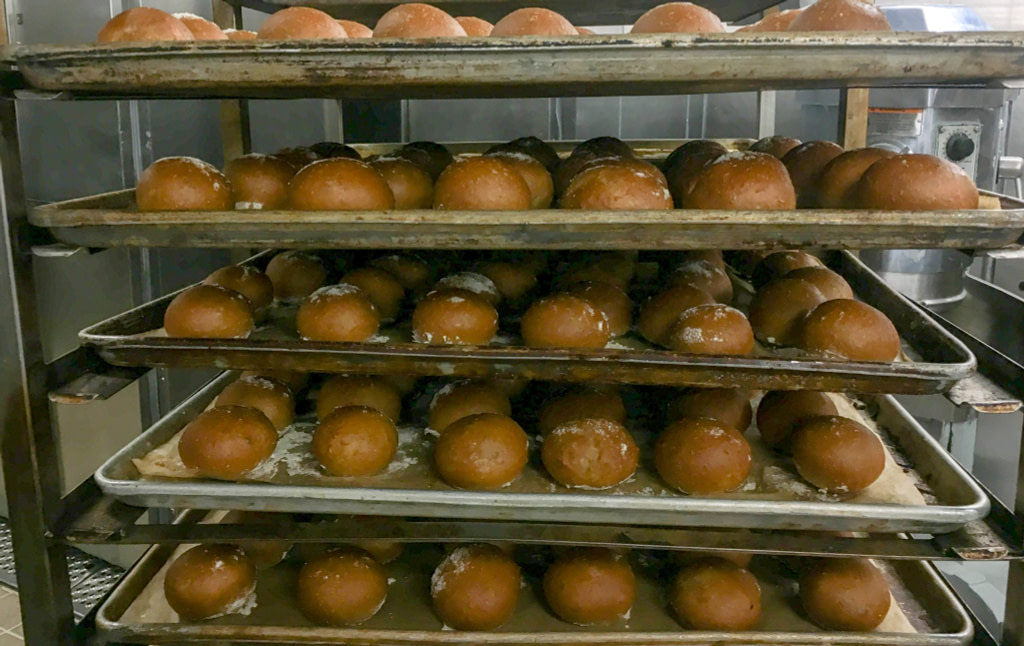 five trays of freshly baked bread rolls stacked on top of each other
