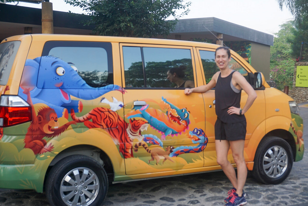 Young woman in black shorts and singlet next to yellow bali zoo branded vehicle