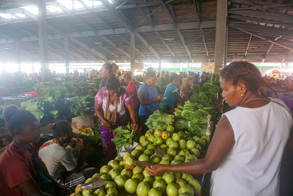 woman paying storeholder for fruit at island market