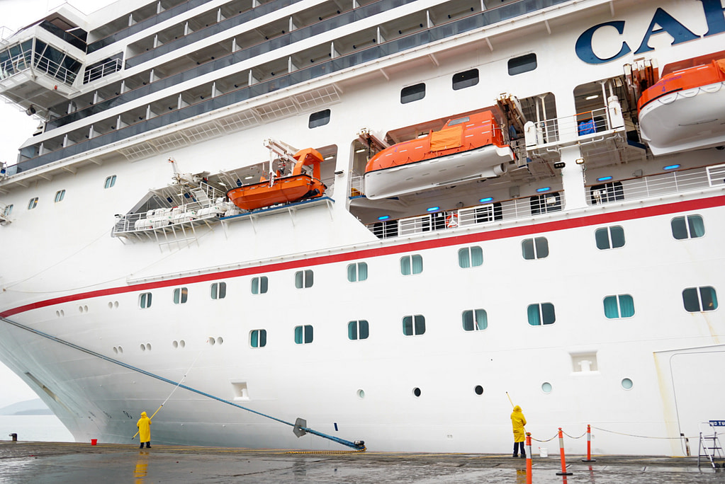 two people in yellow raincoats clean Carnival Splendor from wharf in Noumea