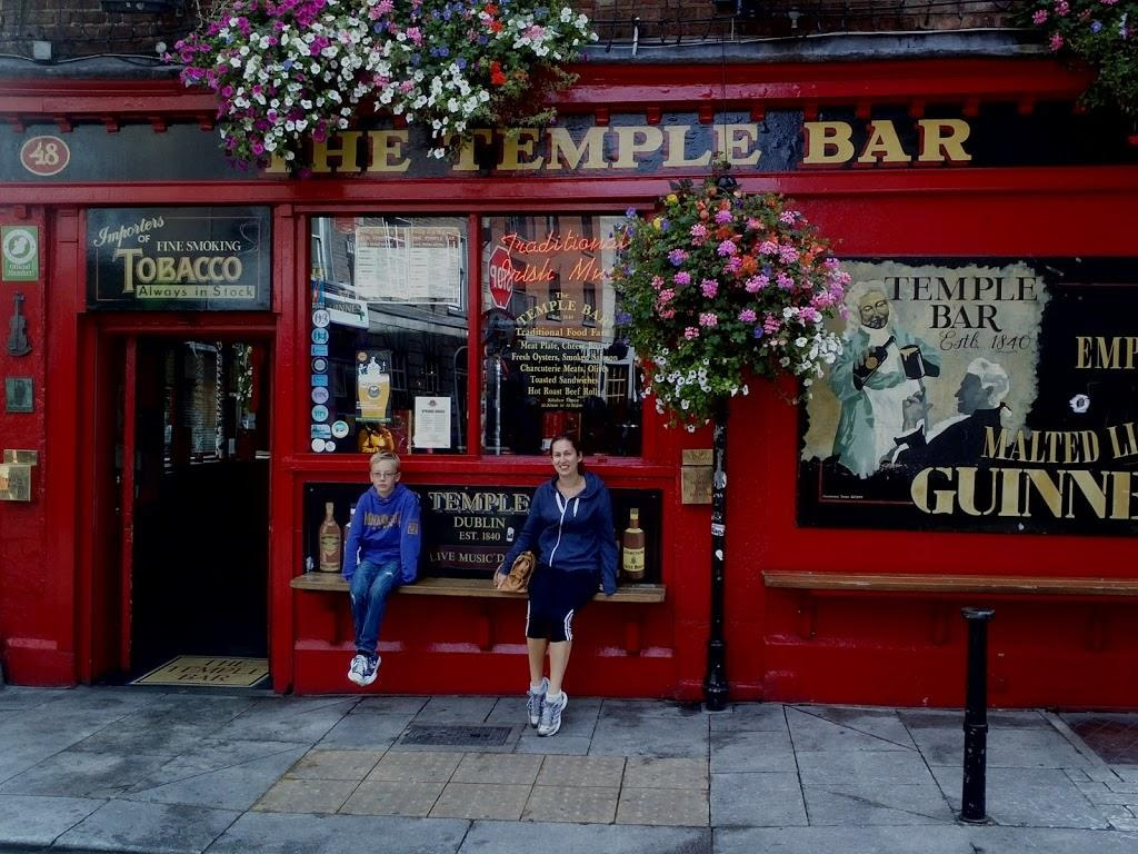 boy and young woman sitting outside red temple bar pub