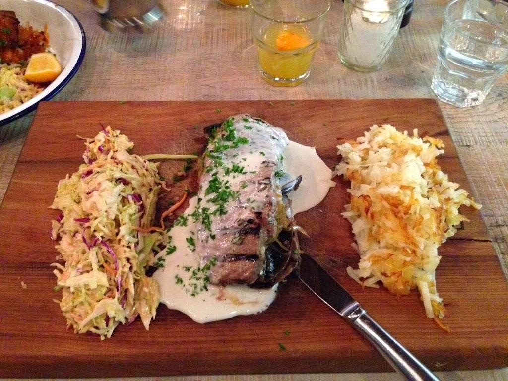 steak served on wooden platter with coleslaw and potato hash