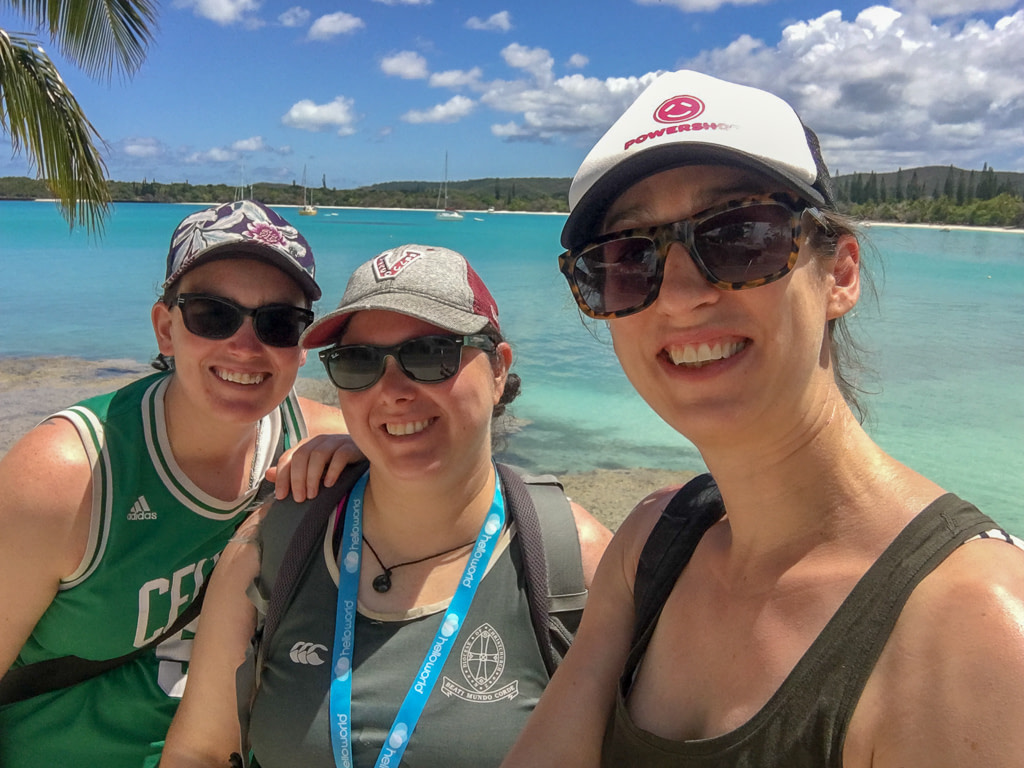 selfie of three young woman with sea, boats and green island in background