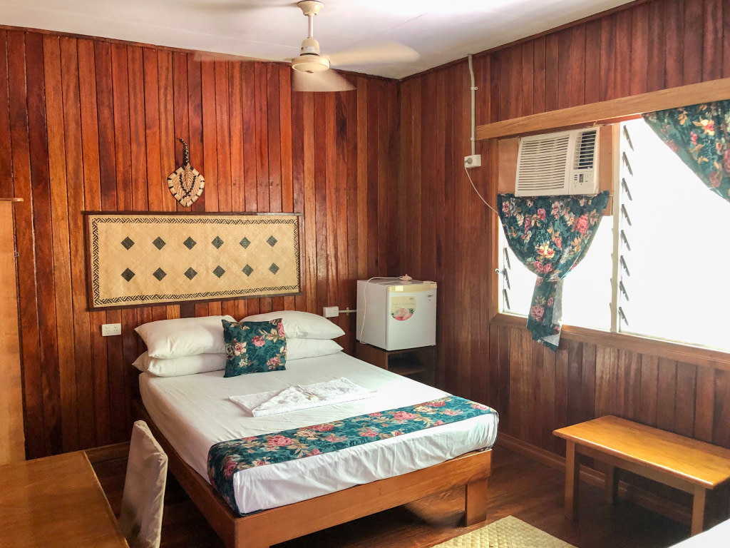 double bed with white linen in wooden paneled motel room with ceiling fan and floral accents