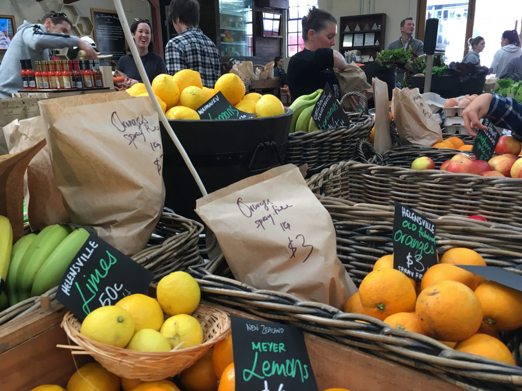 Fresh produce on display with paper bags at Hobsonville Point Markets