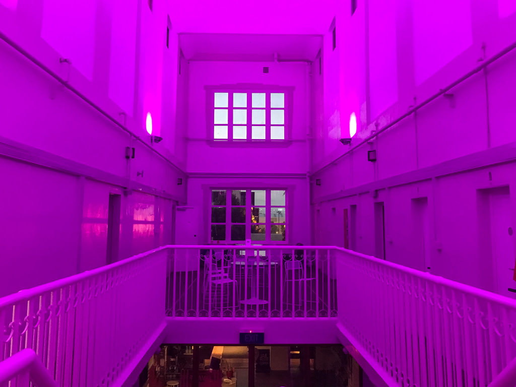 Inside Jailhouse Accommodation lit up pink at night