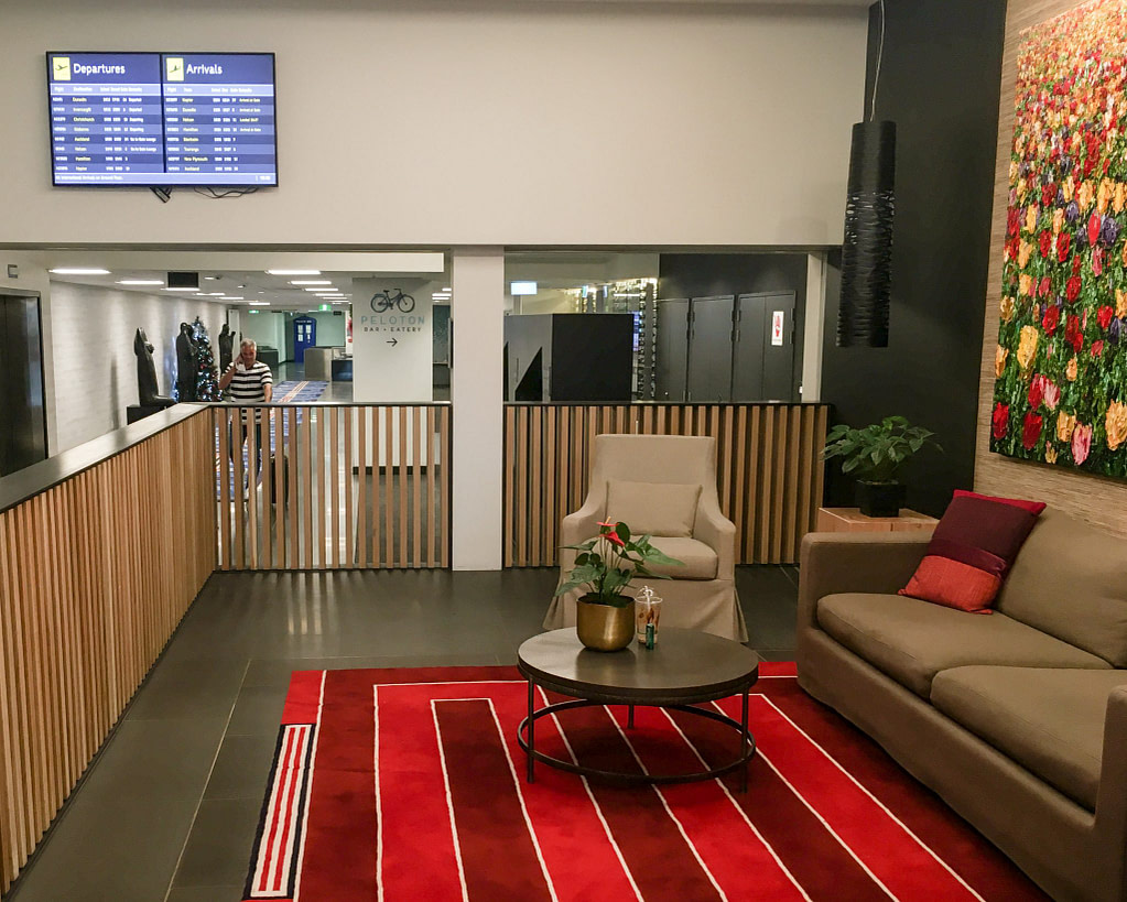 Rydges Wellington Airport lounge area with tan couch, table, red carpet and departures board