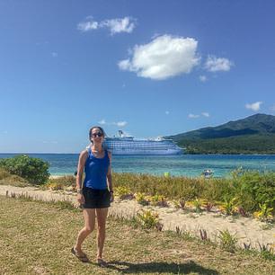 girl posing on green island in front of turquoise water and cruise ship