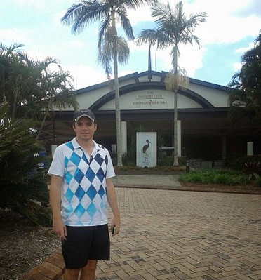 young man in golf clothing stands outside the country club and sanctuary cove golf
