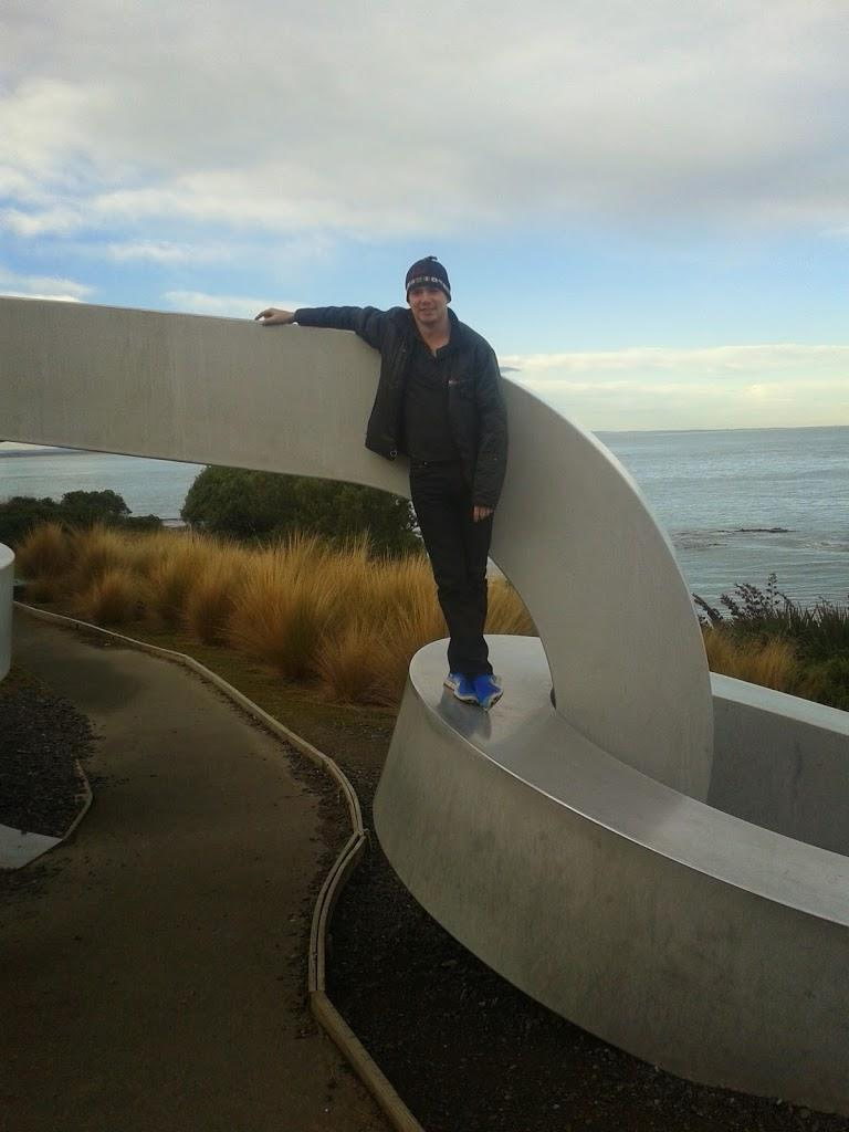 Man on chain sculpture Stirling Point Bluff New Zealand