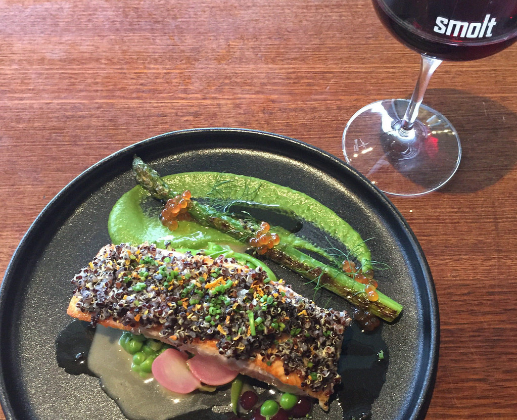salmon dish on black plate with glass of red wine