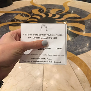 ticket for event held in left hand with grey painted nails over ornate tile floor