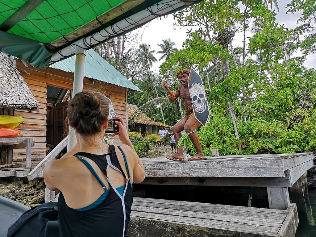 warrior performing cultural welcome in solomon islands while filmed with phone camera